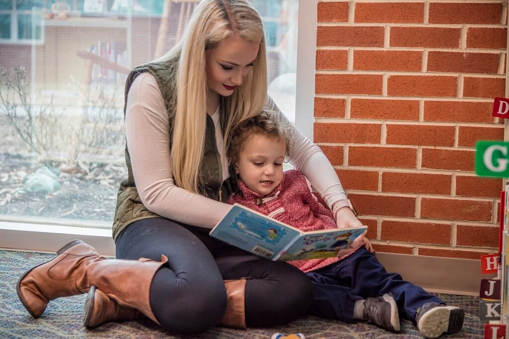 mom reading to child in library