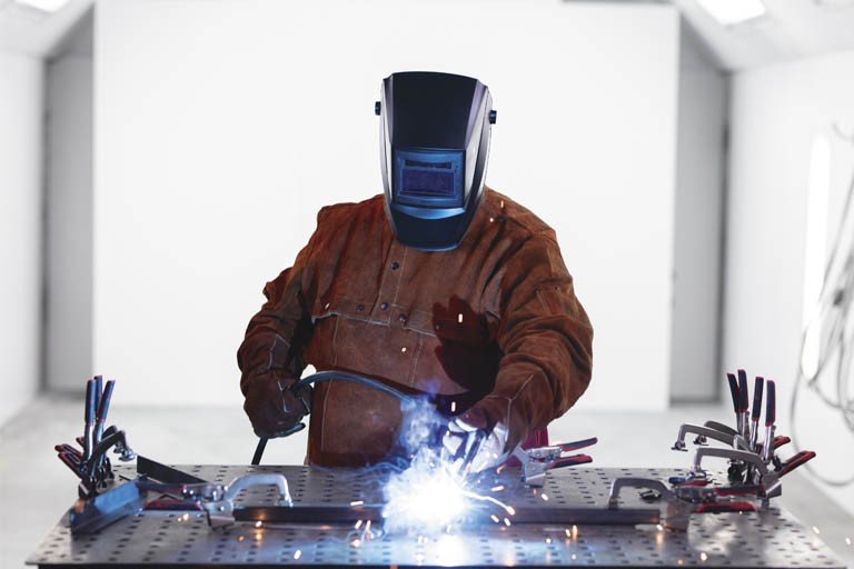 A student welding with a faceshield