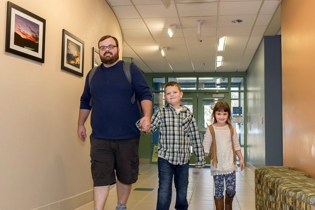 SKCTC father walking through a building on campus with his two children