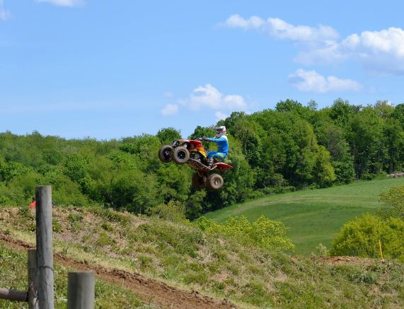 Marshall Smith racing on his four-wheeler. He is airborne in the middle of the dirt track.