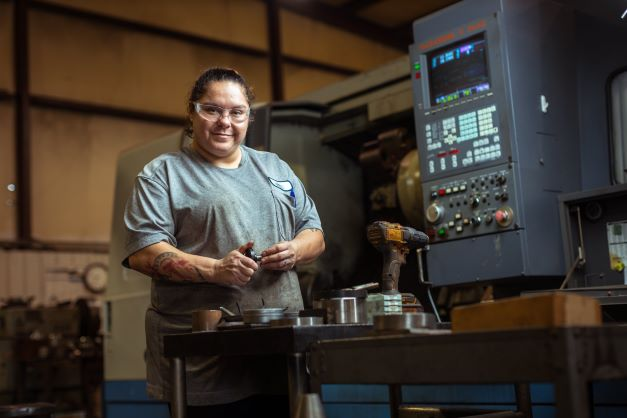 Manid Grubbs poses in front of a CNC machine with a measuring gauge in her hand.