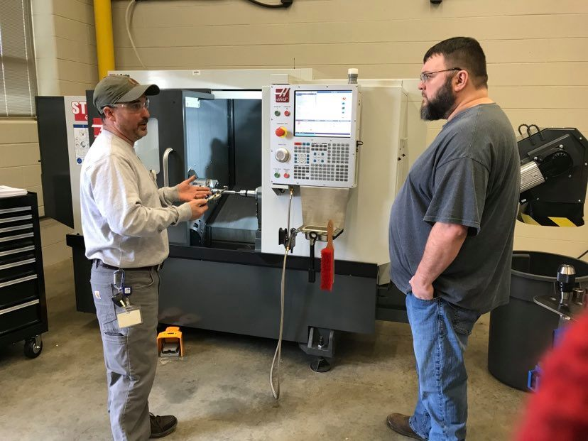 Instructor Michael Carmack teaches a student how to use a piece of manufacturing equipment.