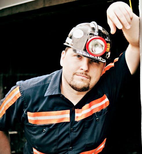 A coal miner wearing a helmet and reflector uniform.