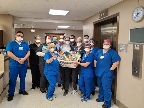 A group of nurses are thanked with a large basket of gifts.