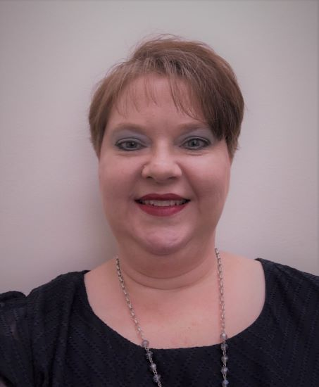 Dr. Melissa Humfleet poses for a selfie with a plain background.