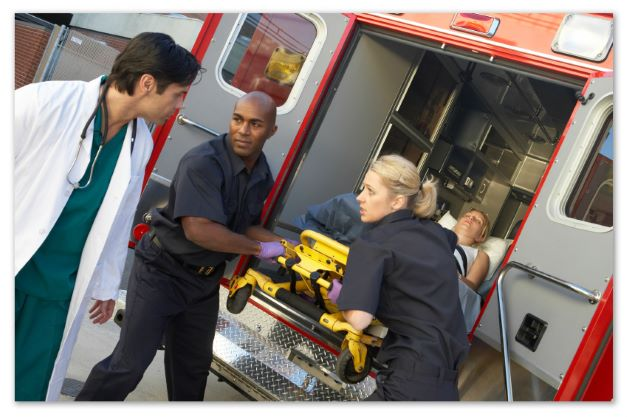 A staged photograph of two paramedics bringing a patient to ER. A doctor is preparing to work with the patient and standing near paramedics.