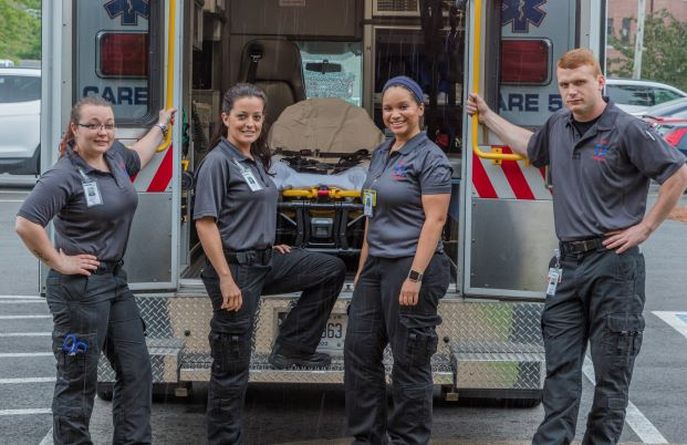 Four paramedic students stand behind an ambulance with open doors.
