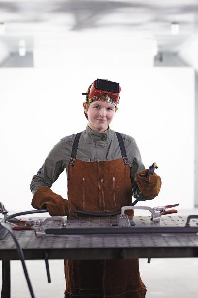 A female welder in a white room.