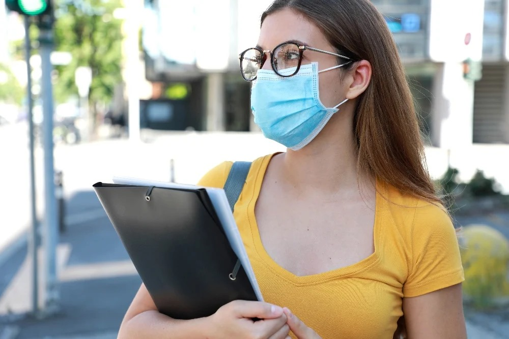 A girl in a yellow shirt is wearing a blue face mask. She is holding a clipboard.