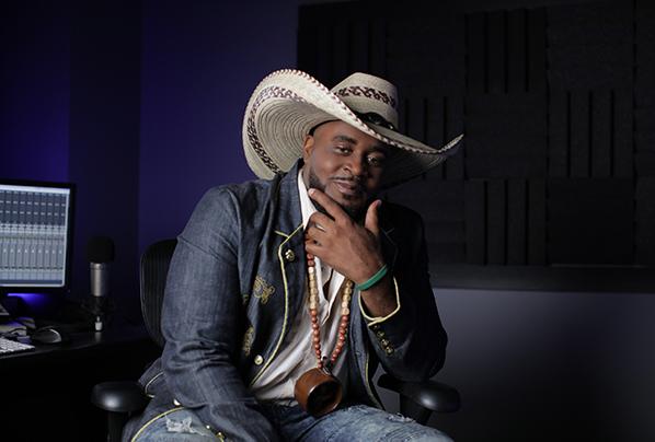 Rapper B Stille sitting in a music studio with a big cowboy hat.